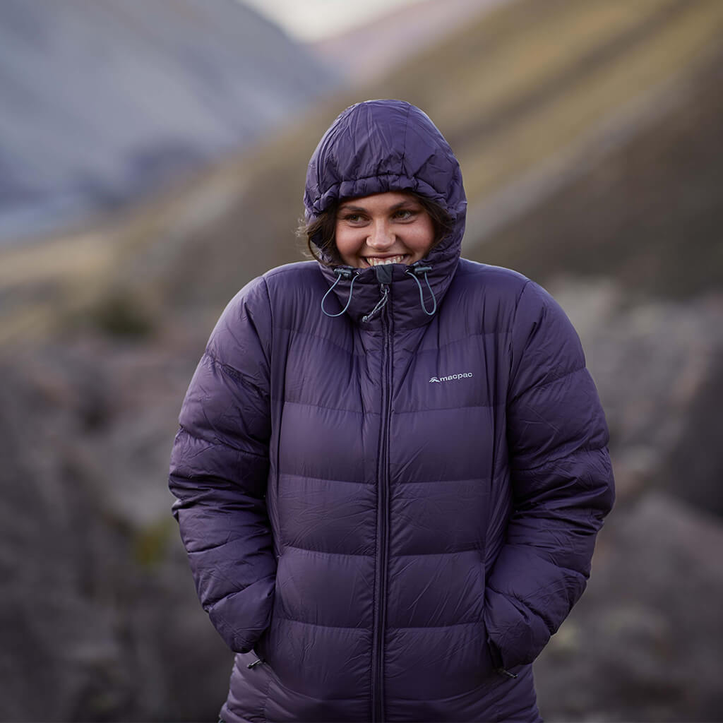 A woman wearing a dark purple macpac puffer jacket with the hood up, standing in a valley