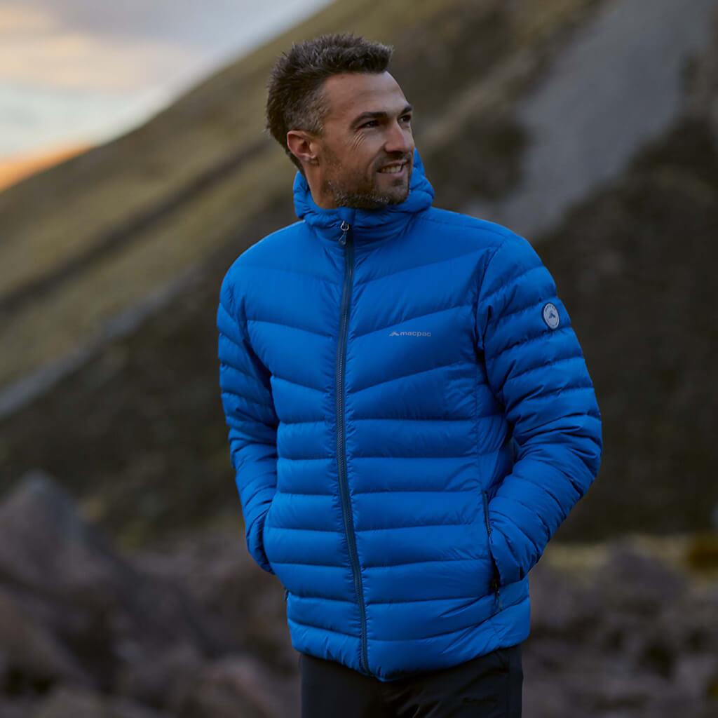 A man wearing a bright blue macpac Mercury jacket on a shady day