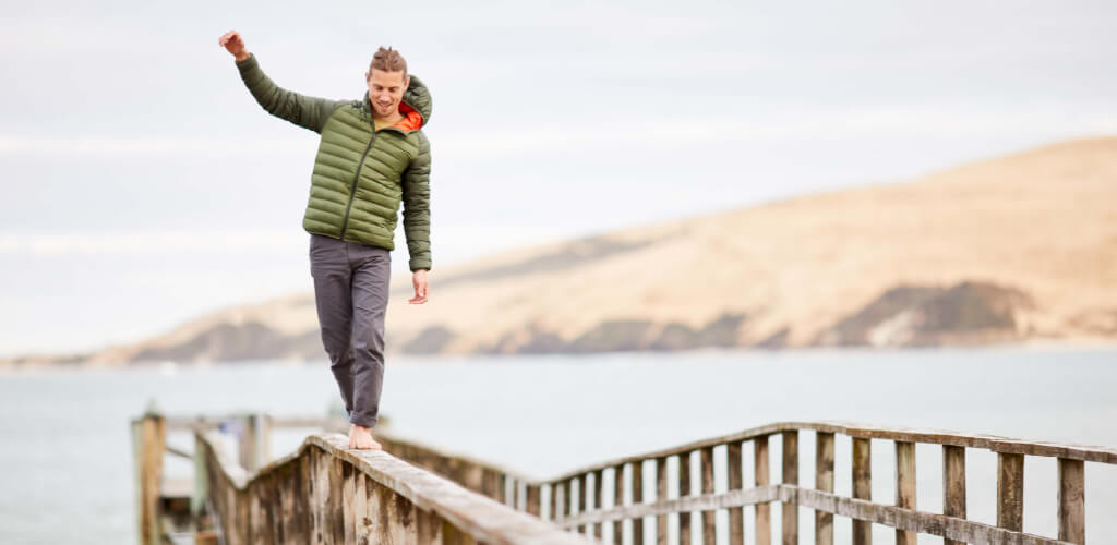 person balancing on wharf wearing green Uber Jacket