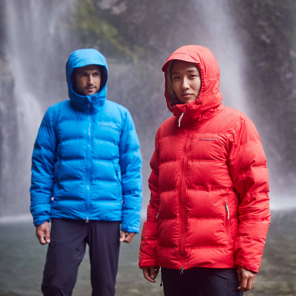 A man and woman wearing blue and red hooded equinox jackets in front of a waterfall