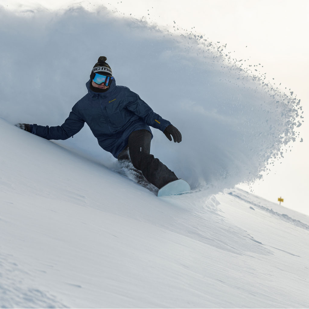 Snowboarder carving a turn in deep powder wearing a dark blue jacket and black pants