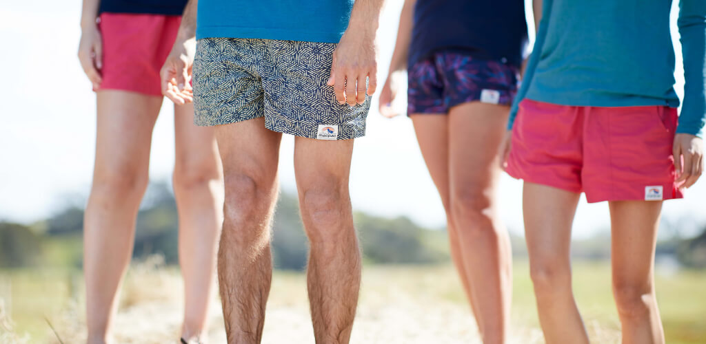 4 people's legs standing wearing winger shorts